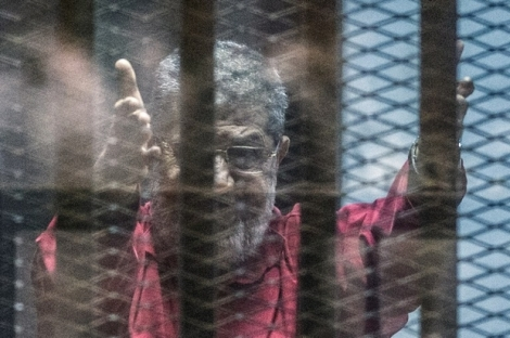 """Egypt's ousted Islamist president Mohamed Morsi, wearing a red uniform, gestures from behind the bars during his trial in Cairo at the police academy in Cairo on April 23, 2016. An Egyptian court postponed its verdict and sentence in the trial of ousted Islamist president Mohamed Morsi, who is charged with spying for Qatar. The head judge of the criminal court said the verdict was postponed to """"May 7 to continue consultations,"""" in brief remarks aired on television. / AFP PHOTO / KHALED DESOUKI"""