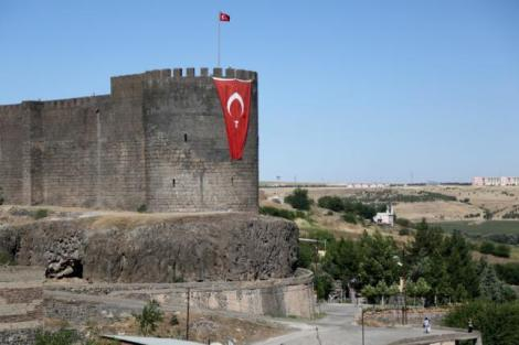 A Turkish flag hangs on the historical city walls at one of the entrance of Sur district in Diyarbakir, Turkey July 11, 2016. REUTERS/Sertac Kayar