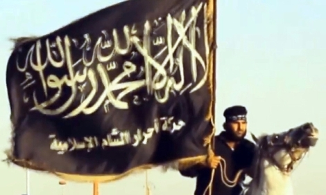 "An image grab taken from a propaganda video uploaded on September 7, 2013 by Syria's Islamist Ahrar al-Sham group shows one of its member holding the group's flag during a parade at an undisclosed location in Syria. Syria's Islamist Ahrar al-Sham rebel brigade named new chiefs on September 10, 2014 after a devastating blast that killed nearly 30 members of its leadership in northeastern Idlib province. Ahrar al-Sham is a key component in the Islamic Front rebel coalition, which has been battling both President Bashar al-Assad's regime, and jihadists from the Islamic State group.  AFP PHOTO / HO / AHRAR AL-SHAM  === RESTRICTED TO EDITORIAL USE - MANDATORY CREDIT ""AFP PHOTO / HO / AHRAR AL-SHAM "" - NO MARKETING NO ADVERTISING CAMPAIGNS - DISTRIBUTED AS A SERVICE TO CLIENTS FROM ALTERNATIVE SOURCES, AFP IS NOT RESPONSIBLE FOR ANY DIGITAL ALTERATIONS TO THE PICTURE'S  === / AFP PHOTO / AHRAR AL-SHAM / -"