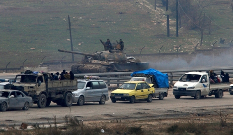 Forces loyal to Syria's President Bashar al-Assad sit on a tank as a convoy of buses and other vehicles bringing people out of eastern Aleppo turns back in the direction of the besieged rebel enclave, Syria December 16, 2016. REUTERS/Omar Sanadiki - RTX2VBYA
