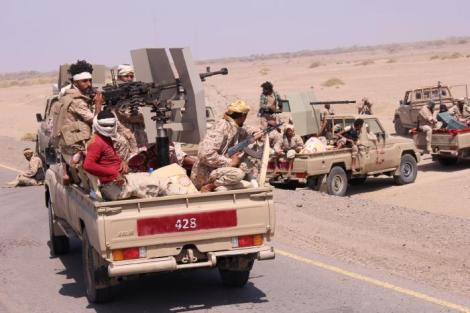 Members of the Yemeni army ride on the back of military trucks near the Red Sea coast city of al-Mokha