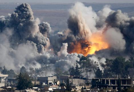 "Smoke rises over Syrian town of Kobani after an airstrike, as seen from the Mursitpinar border crossing on the Turkish-Syrian border in the town of Suruc in this file October 18, 2014 file photo.   A U.S.-led military coalition has been bombing Islamic State fighters who hold a large swathe of territory in both Iraq and Syria, two countries involved in complex multi-sided civil wars in which nearly every country in the Middle East has a stake.    The Turkish military and police had declared the Turkish-Syrian border area a ""military zone"", which limits the ability of the press to move around.   In these days of modern warfare, the weaponry is more powerful than that in the old days. So all of my colleagues and I have to be doubly careful to ensure we do not end up in the line of fire, as positions of Kurdish YPG fighters and IS militants change quickly.   For all those reasons, to stay away is the only solution at the moment.   We ended up on hills about 2km (1.24 miles) away from Kobani using very long telephoto lenses, often more than 1000mm, to get a peek into the city while listening to the sound of war and smelling its scent.    Sometimes you see a shadow of a fighter hiding behind a building and more often you see the massive impact of heavy airstrikes.   It is a bit strange sitting there with lenses I usually use for sports photography alongside people from the area, who come to the hills to see what's going on.  They bring binoculars and make tea - making it almost seems like a tourist attraction. - Kai Pfaffenbach       REUTERS/Kai Pfaffenbach (TURKEY - Tags: MILITARY POLITICS CONFLICT TPX IMAGES OF THE DAY)  ATTENTION EDITORS: THIS PICTURE IS PART OF THE PACKAGE 'PICTURES OF THE YEAR 2014 - THE PHOTOGRAPHERS' STORY'. SEARCH 'PHOTOGRAPHERS' STORY' FOR ALL IMAGES' - RTR4FOX1"