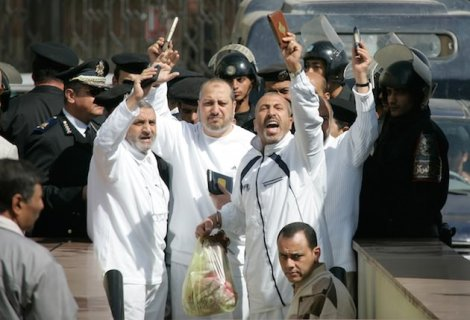 Some of 29 members of the banned Muslim Brotherhood clutch Qurans as the are led into a court in the New Cairo area of Cairo, Egypt Wednesday, Feb. 28, 2007. The court upheld Egypt's prosecution decision to freeze the assets of 29 members of the Muslim Brotherhood for financing a banned organization - causing a heavy loss for the country's most powerful opposition movement, which won 88 of parliament's 454 seats in 2005 elections with its candidates running as independents. (AP Photo/Ben Curtis)